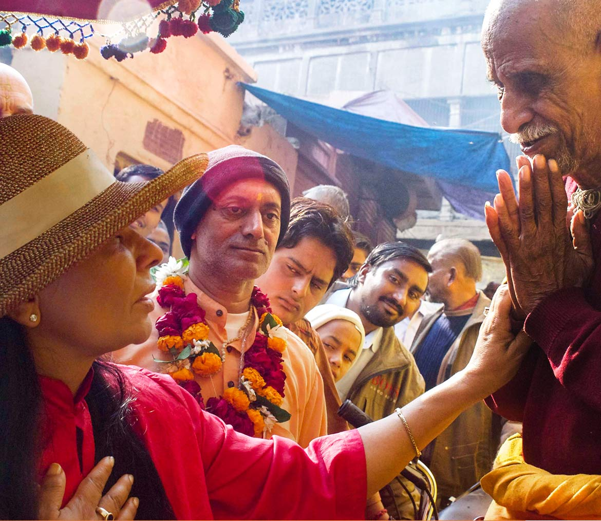 Sai Maa out in the streets of India blessing a man on the street with many on lookers watching.
