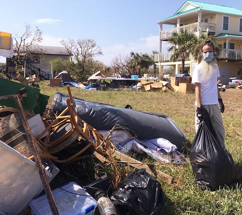 Dayananda removing trash to a pile outside a home.