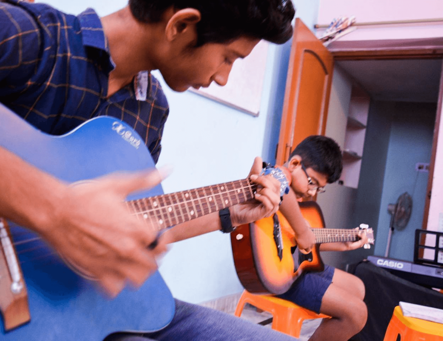 Boys learning the guitar at Melisma.