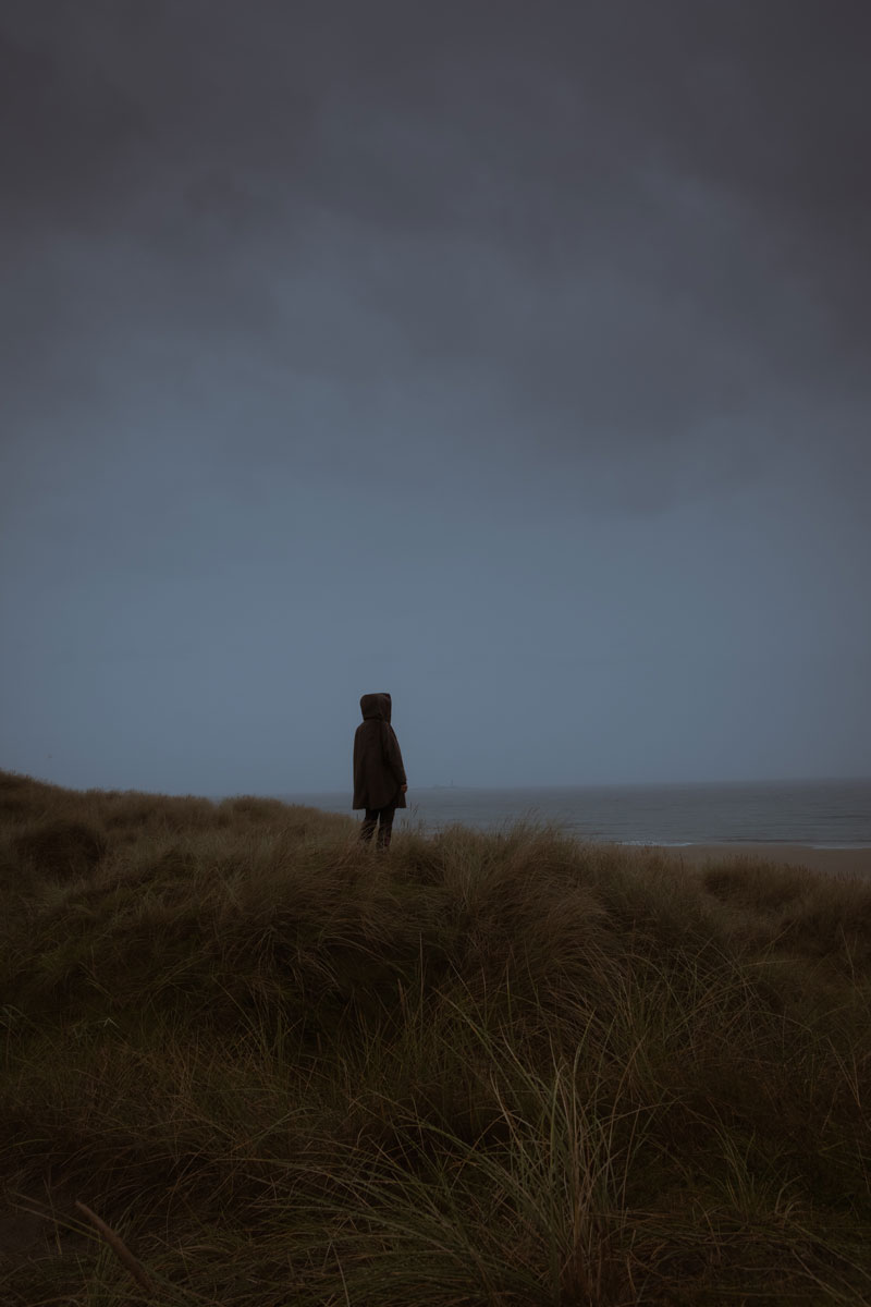 A person wearing a hoodie staring into the ocean