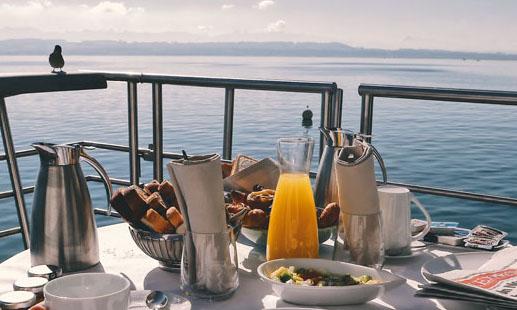 belle table de petit déjeuner dressée sur un balcon, devant la mer et l'horizon