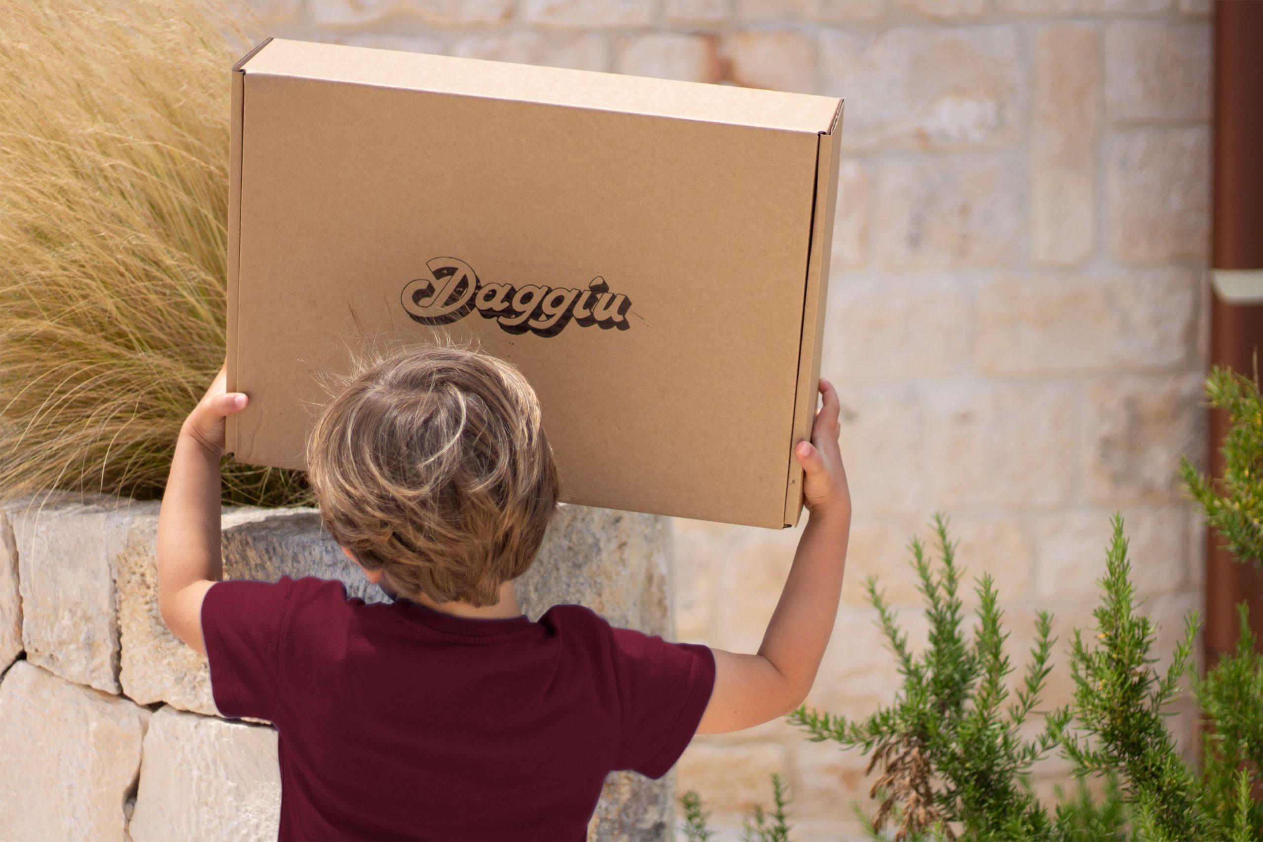 Un bambino regge il pacco da giù che ha ricevuto