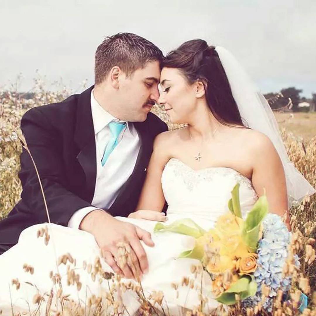 A picture of the owners of our affordable wedding venue, sitting in a country field, with a wedding dress and wedding veil plus wedding bouquet and a wedding tuxedo, heads together, eyes closed, for a magical wedding memory