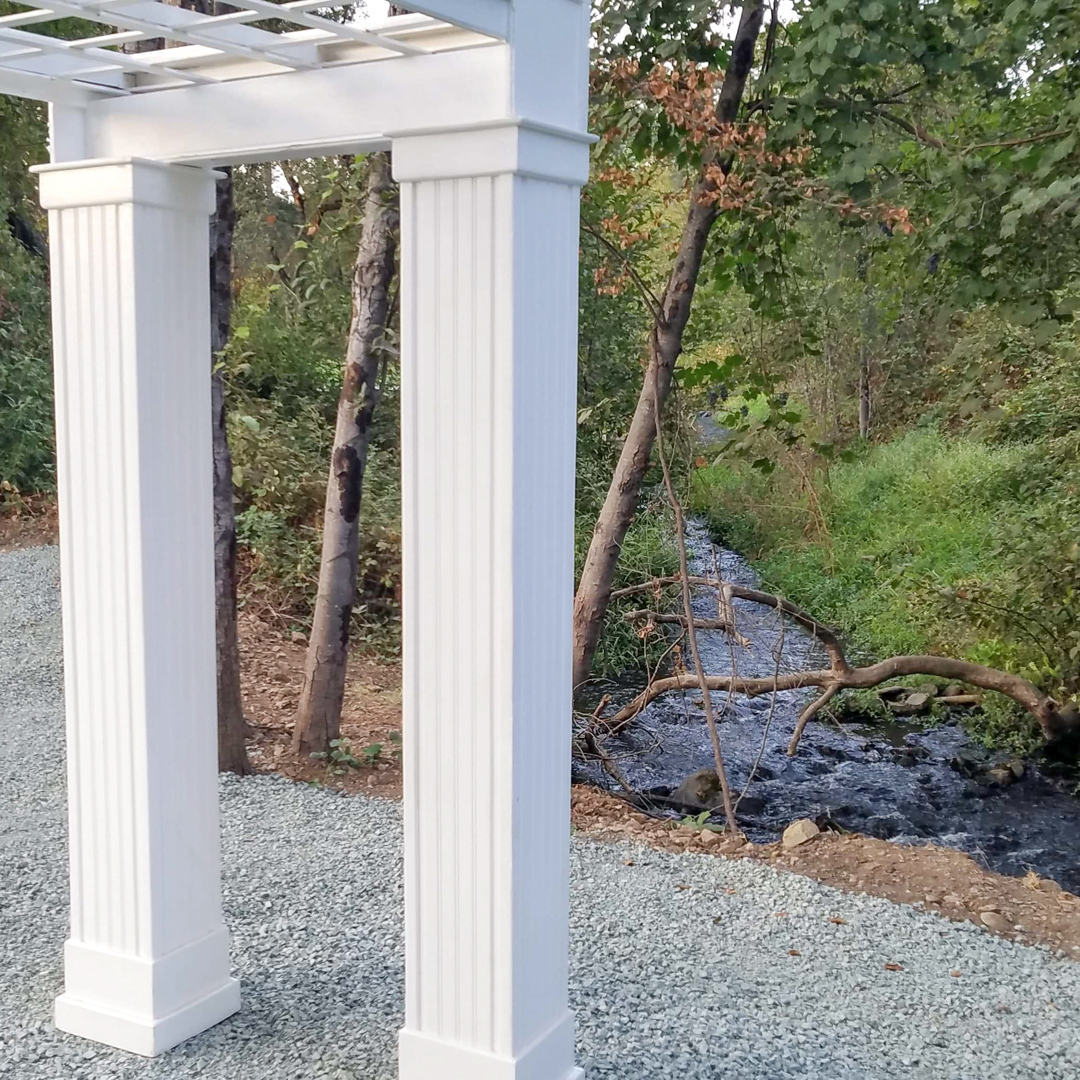 White wedding arbor at creekside ceremony site with creek in the background
