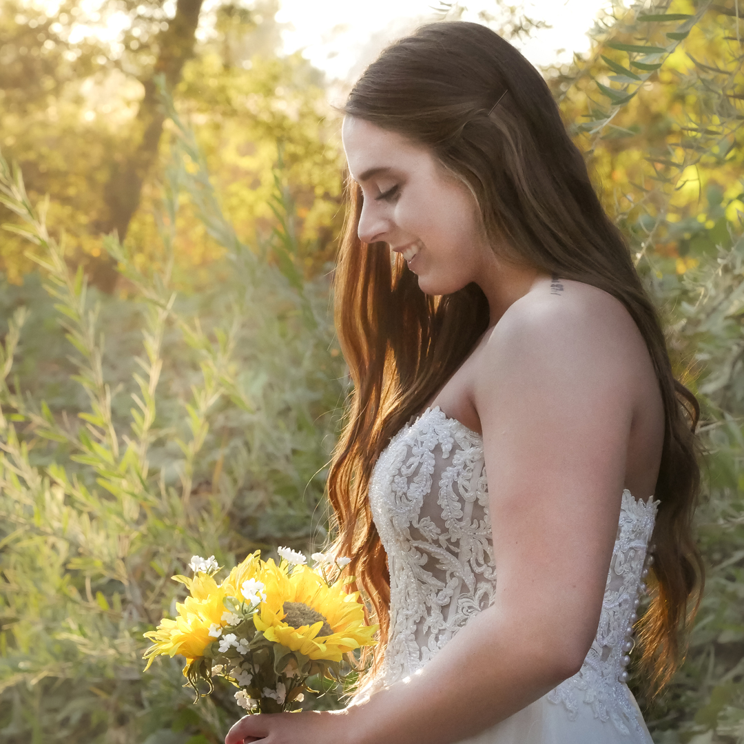 A blushing bride with a sunflower bouquet standing against a natural background
