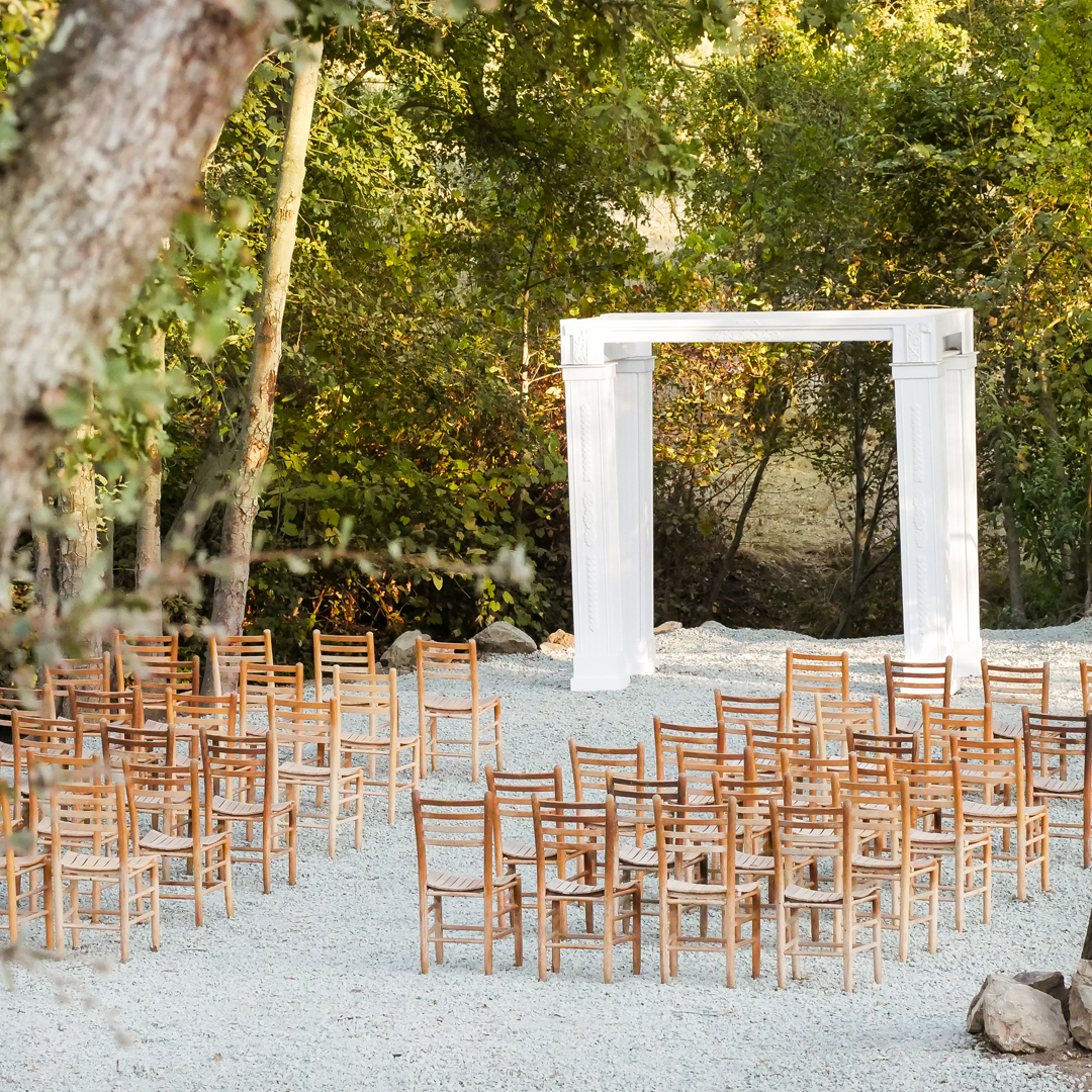 White wedding arbor at creekside ceremony site with rustic chairs and gravel