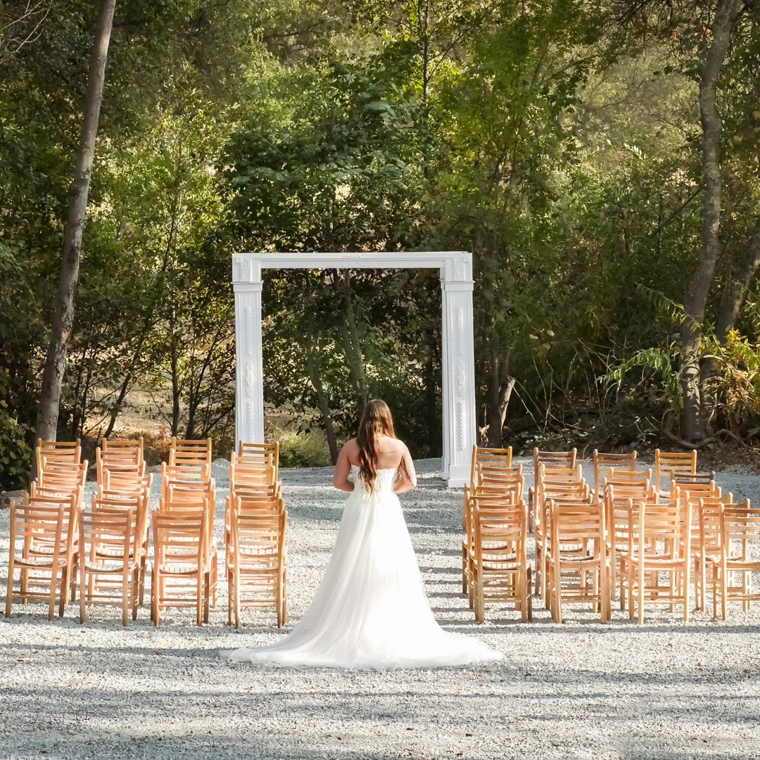 Bride standing in wedding aisle with rustic chairs on each side and a white wedding arbor in front