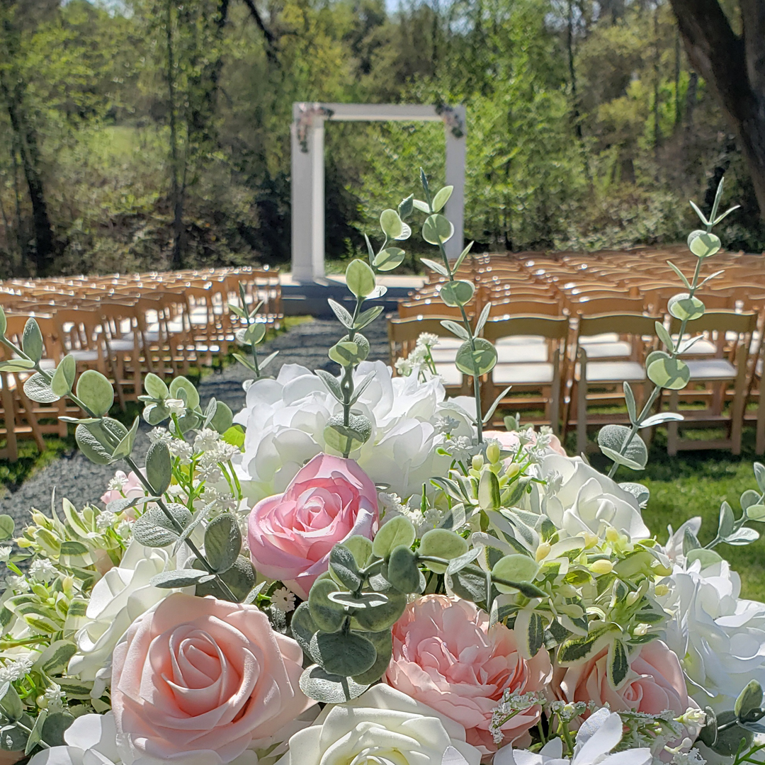 Fake wedding flowers with white and blush roses and greenery bouquet in foreground and ceremony in background