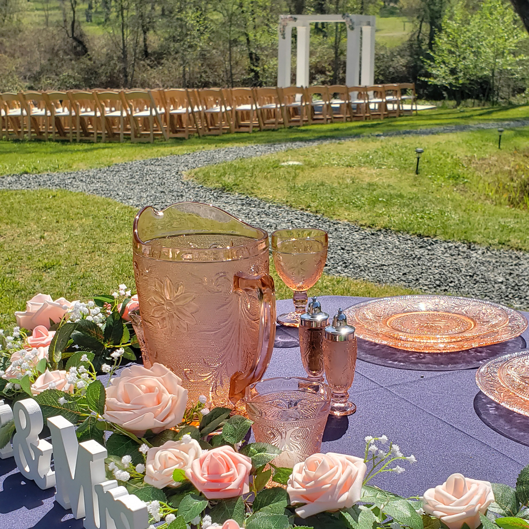 Navy blue wedding sweetheart table with blush colored glassware and ceremony site in background
