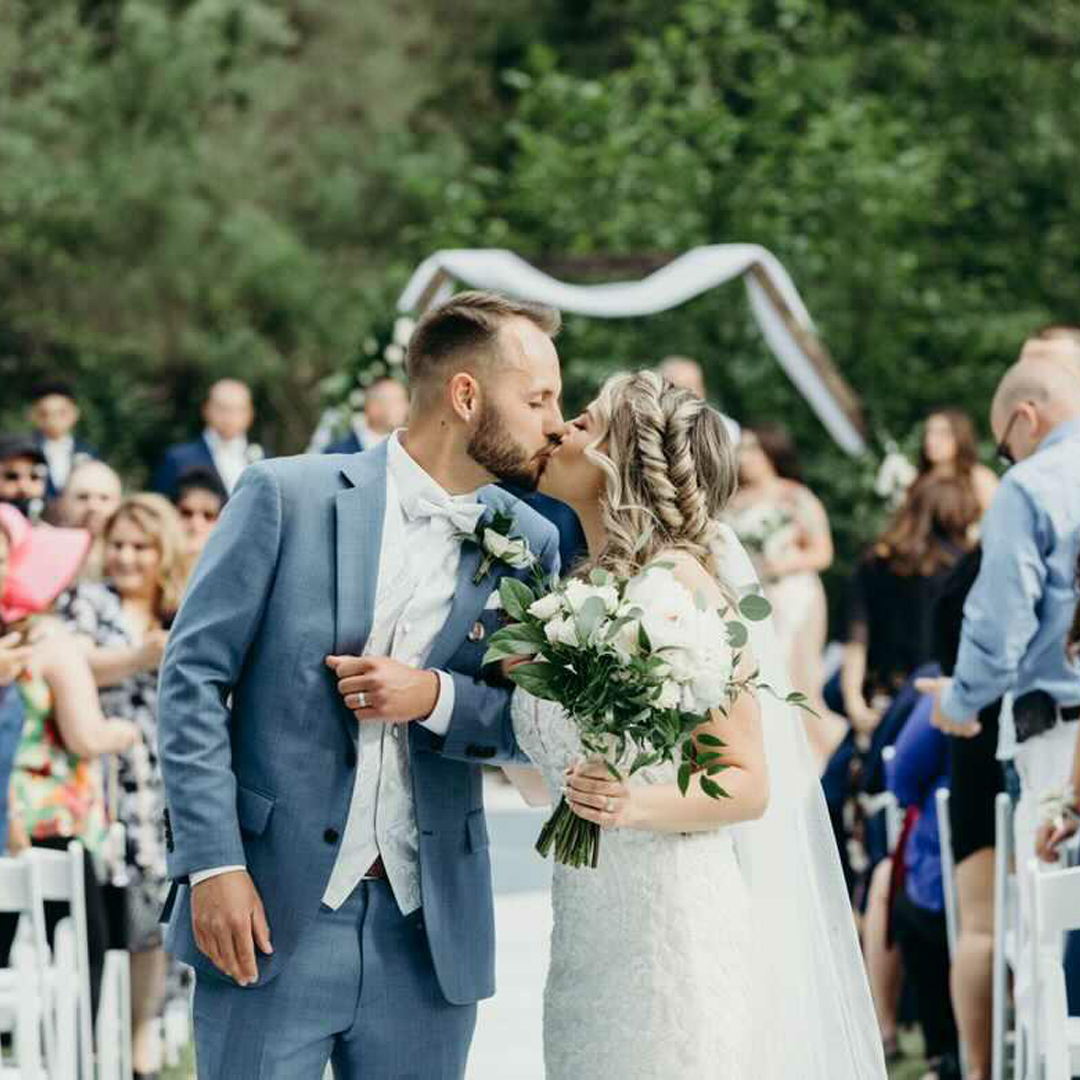 A bride and groom kissing after just saying their I Do's and walking down the aisle at an outdoor ceremony area with greenery