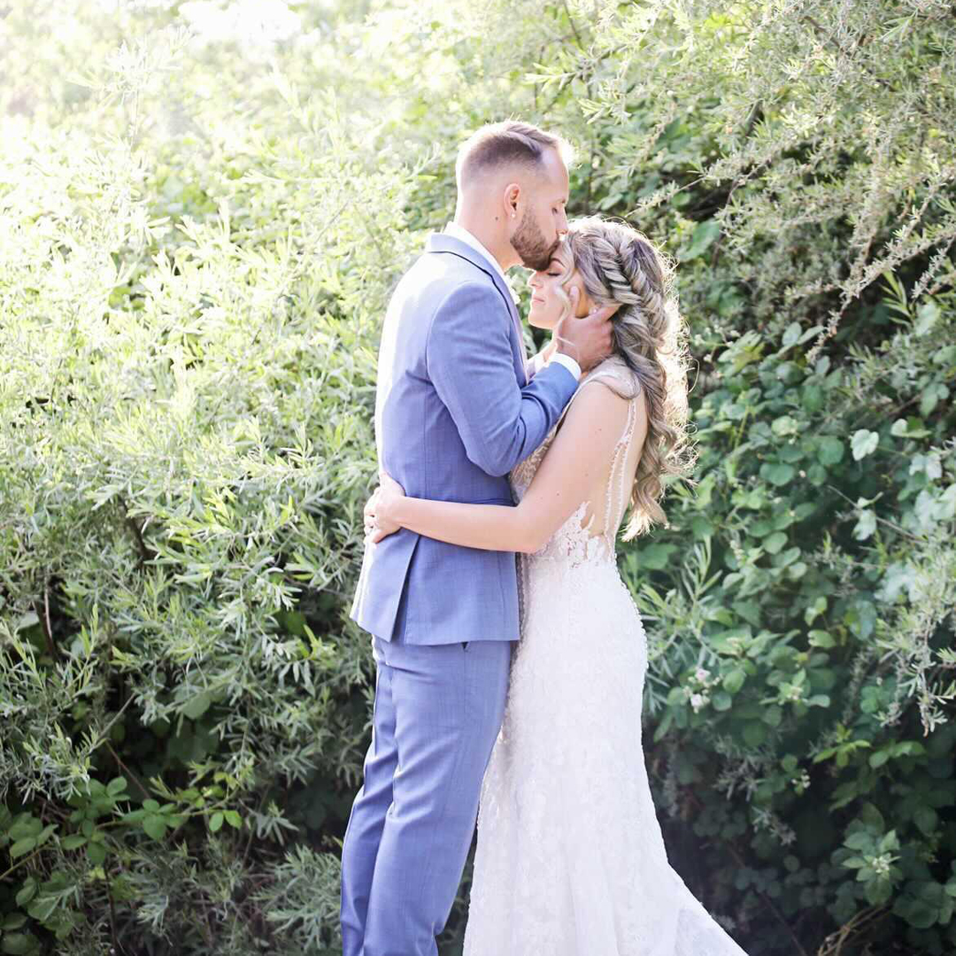 A bride and groom amongst greenery of olive colored willow trees