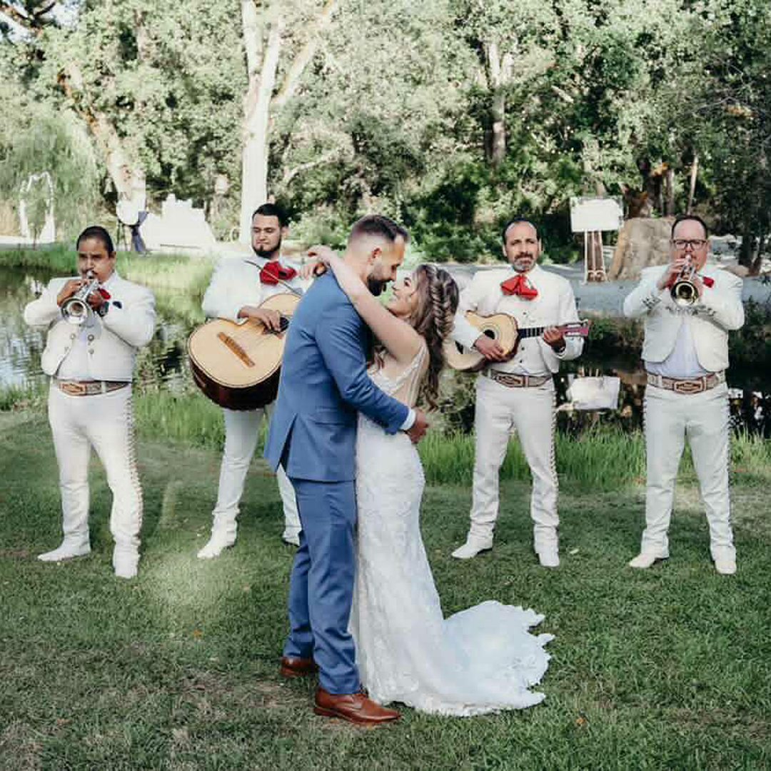 Mariachi band playing at a wedding ceremony with bride and groom in foreground against a pond