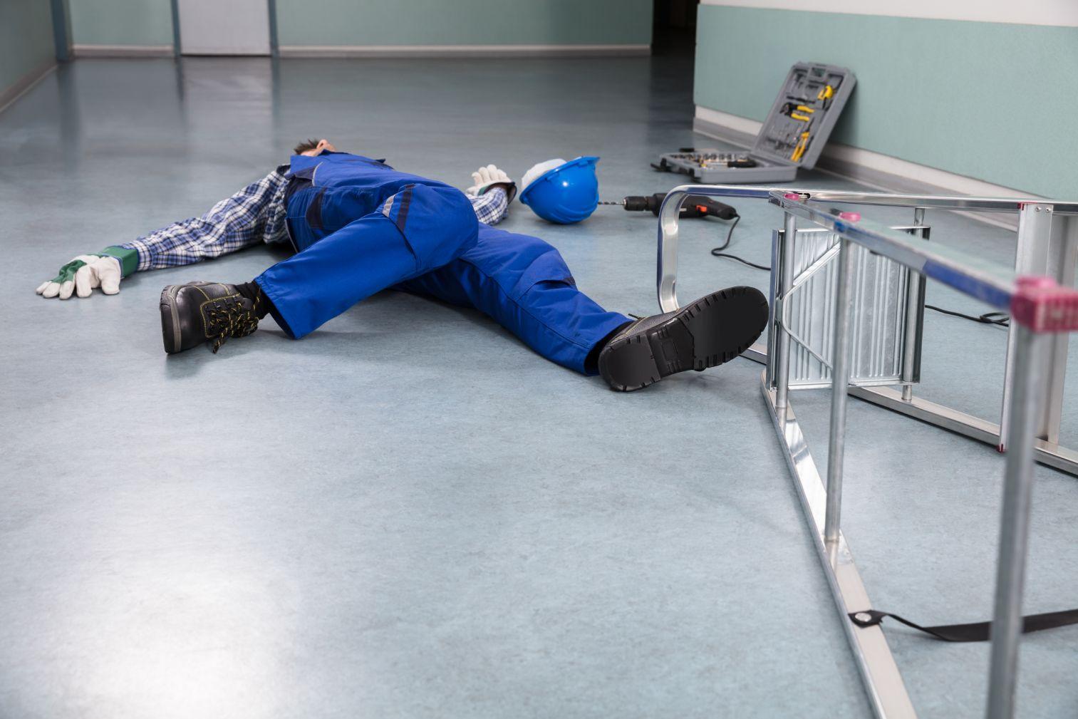 Trabajador en el piso después de caerse de una escalera.