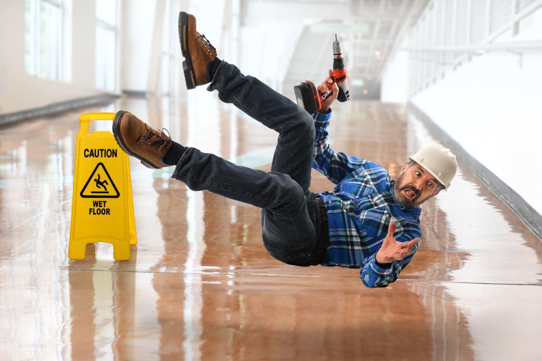 Trabajador deslizando en un piso mojado con taladro en la mano.