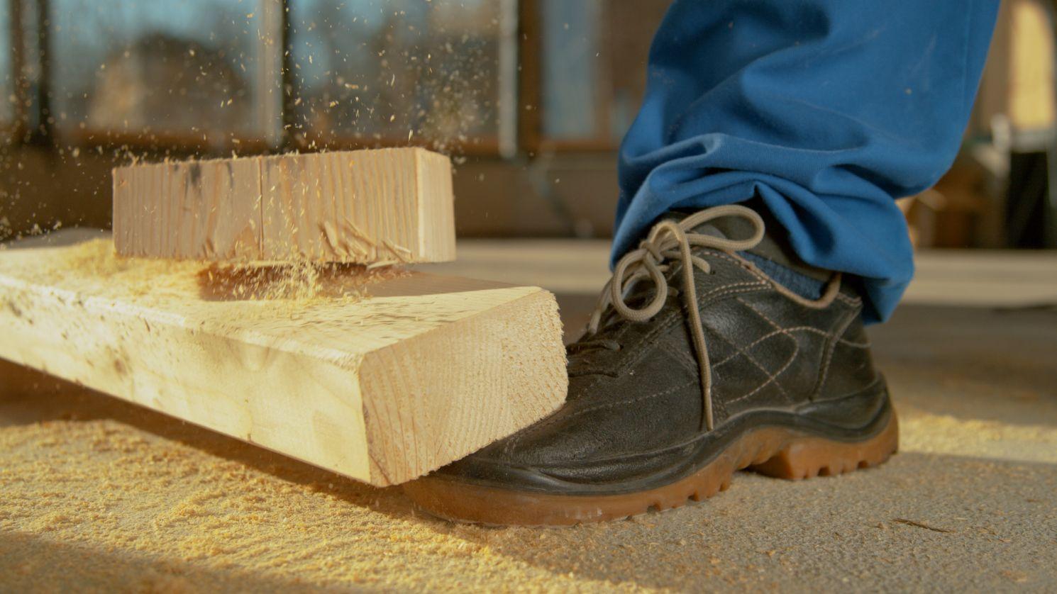 Madera cayendo en un pie de trabajador de construcción.
