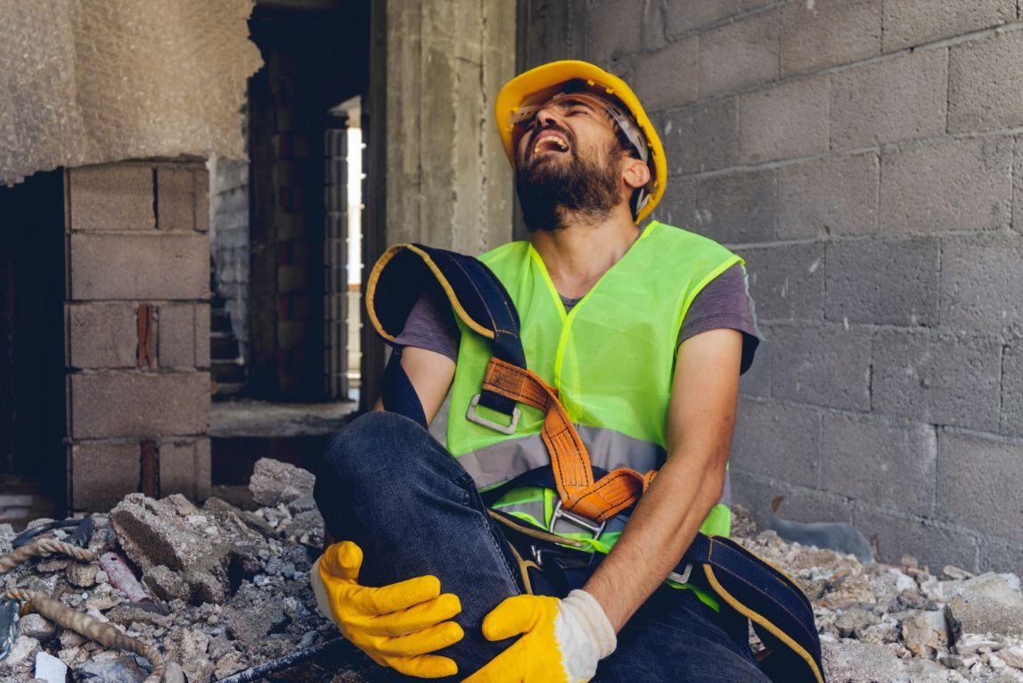 Trabajador de construcción lesionado en la pierna en una obra de construcción.