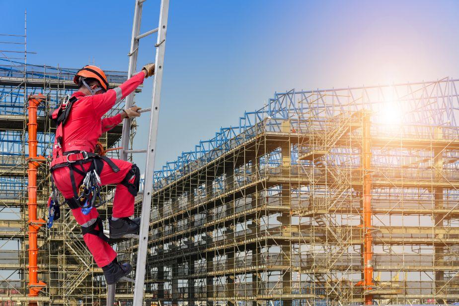 Trabajador subiendo escalera en obra de construcción.