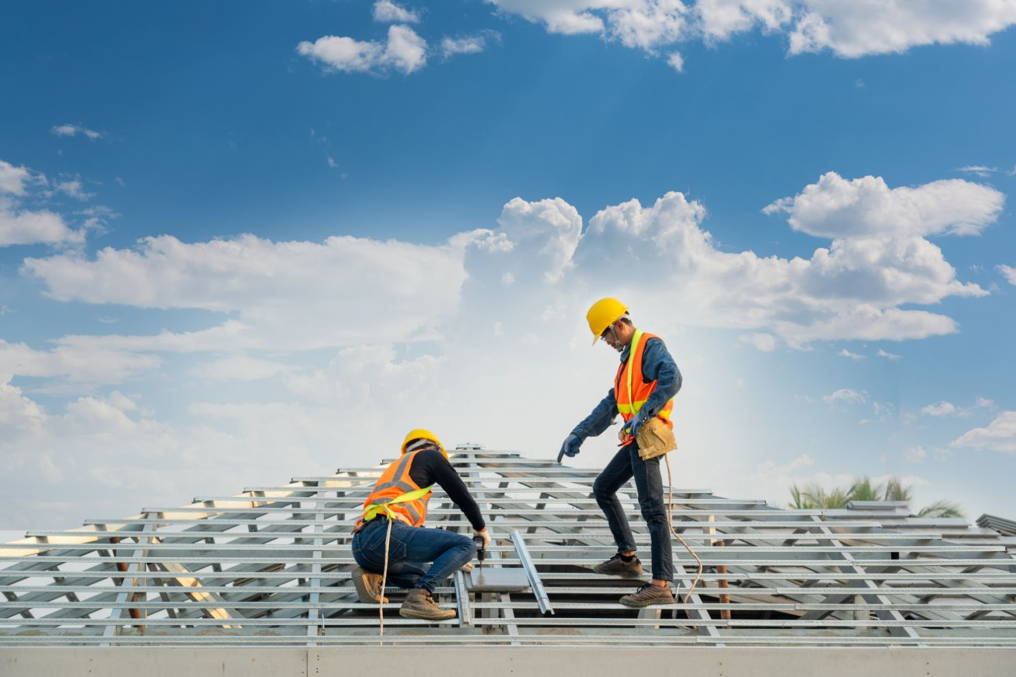 Two construction workers installing panels on a roof.
