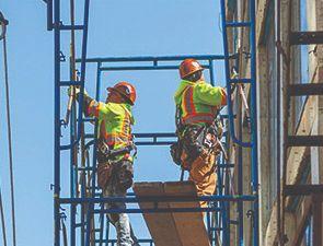 Trabajadores de construccion en un andamio.