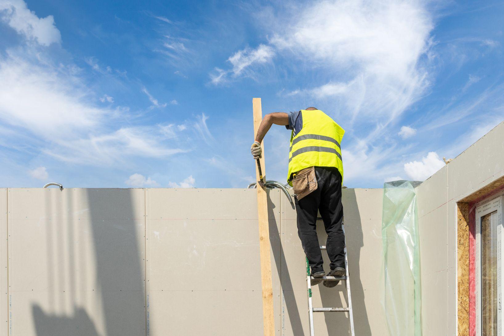 Trabajador usando martillo en una escalera en obra de construcción.