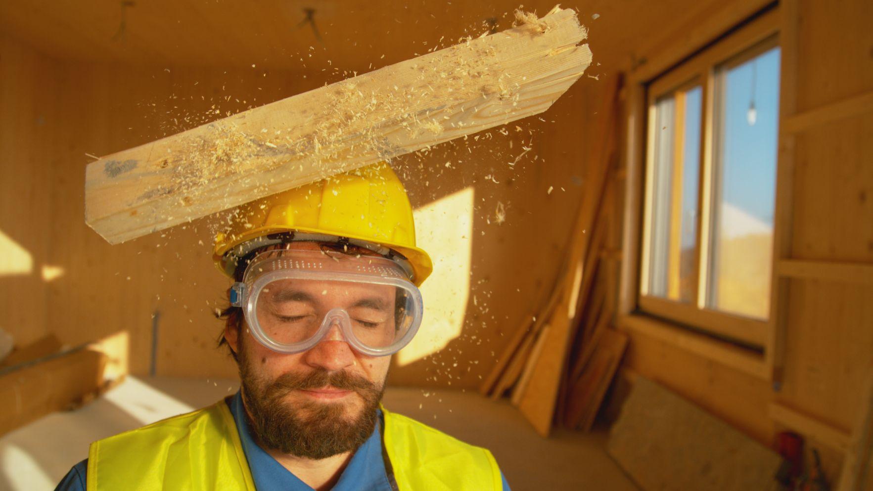 Madera cayendo en casco de seguridad de trabajador de construcción.