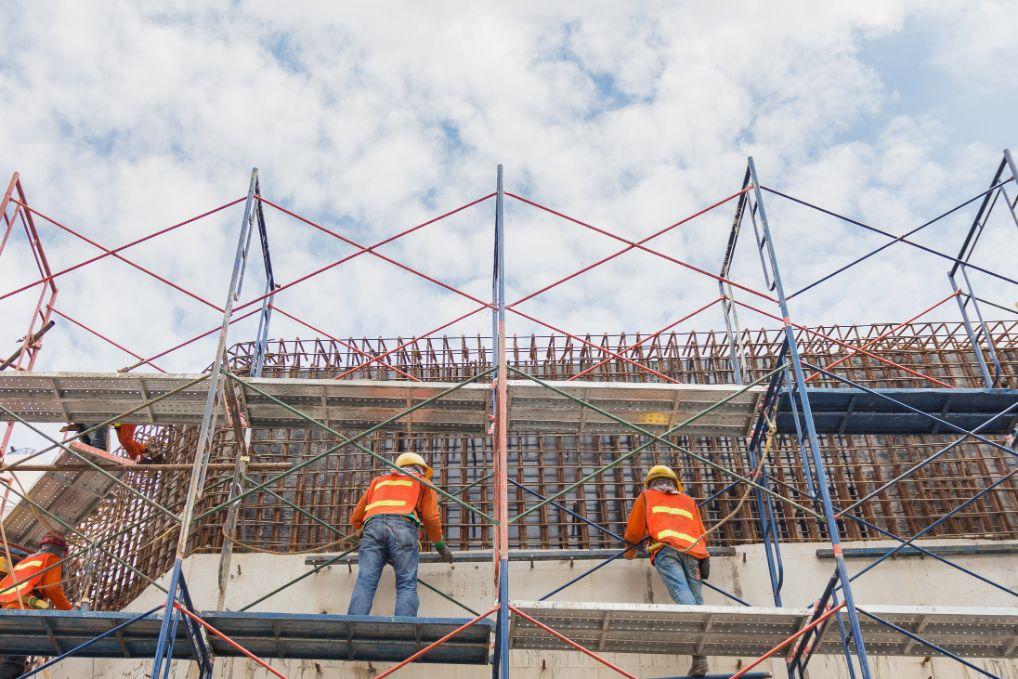 Trabajadores de construcción en un andamio construyendo una pared.