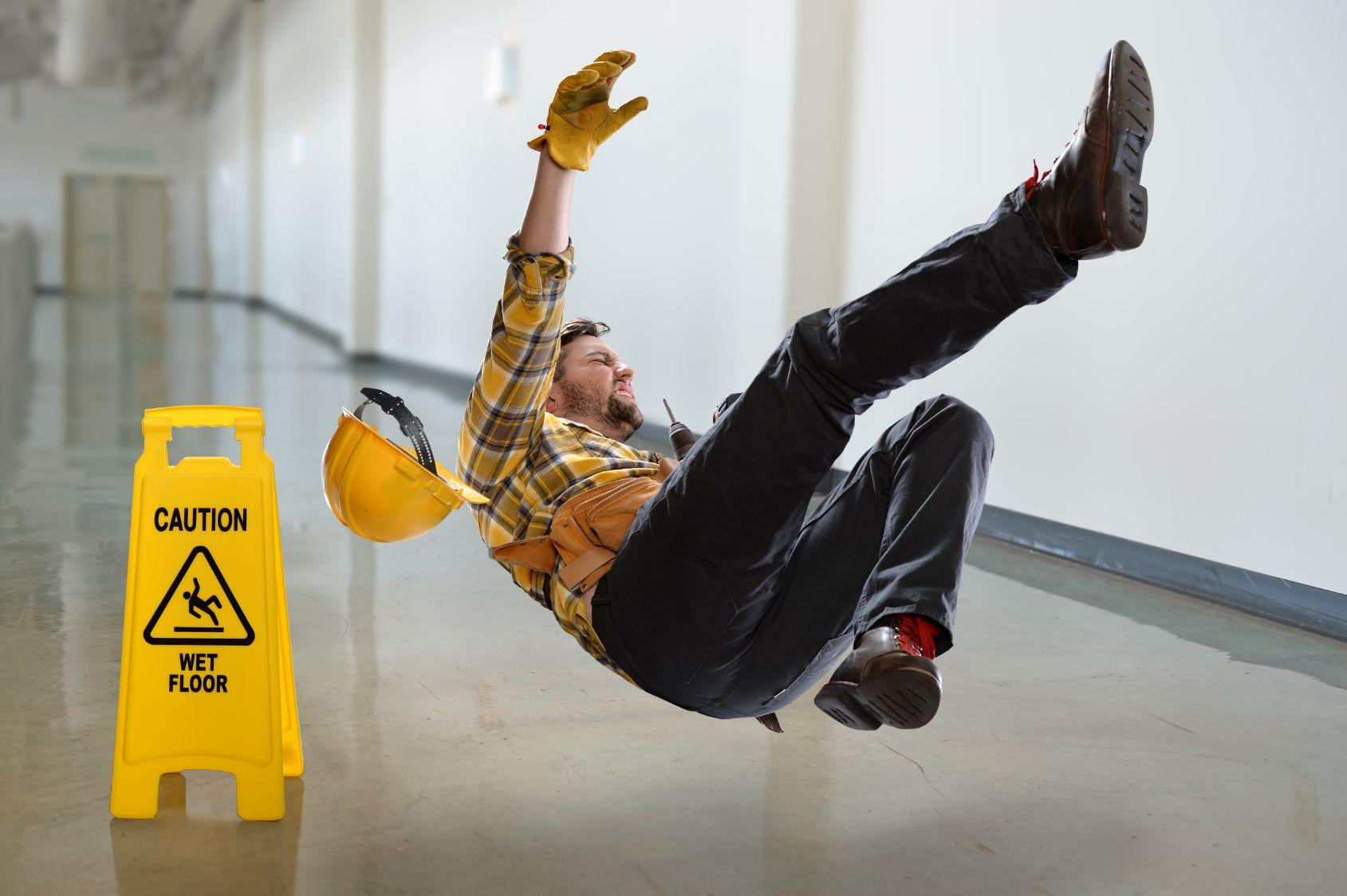 Trabajador de construcción cayendo en una zona con piso mojado.