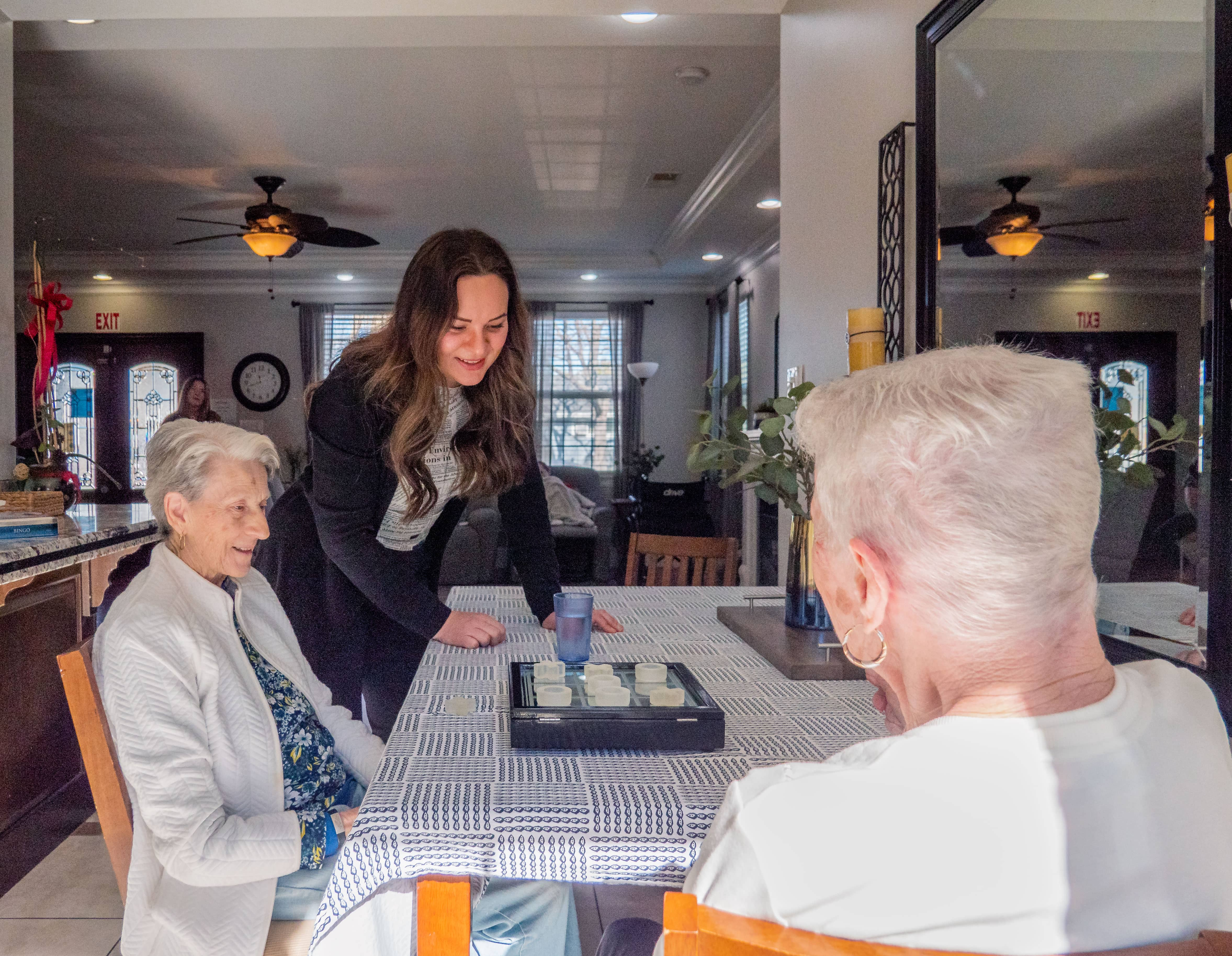 A woman watching two elderly residents play tic tac toe.
