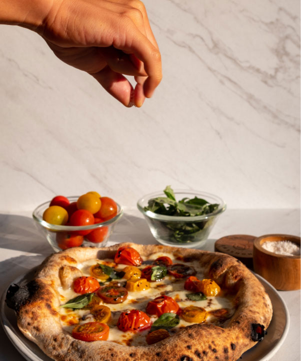 Fingers pinching and tossing Only Salt onto a homemade pizza.