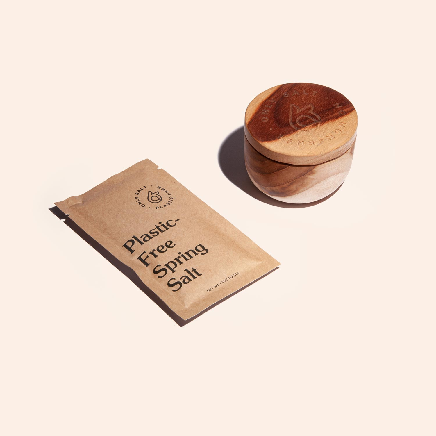 Spring salt packet lays next to a wooden pinch bowl by Only.