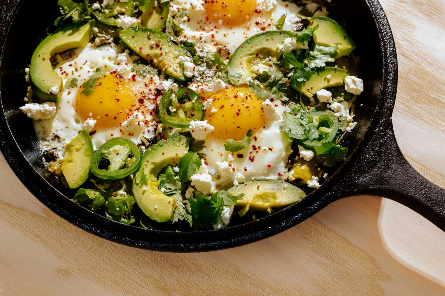 Egg, avocado, and jalapeno meal in a cast iron skillet.