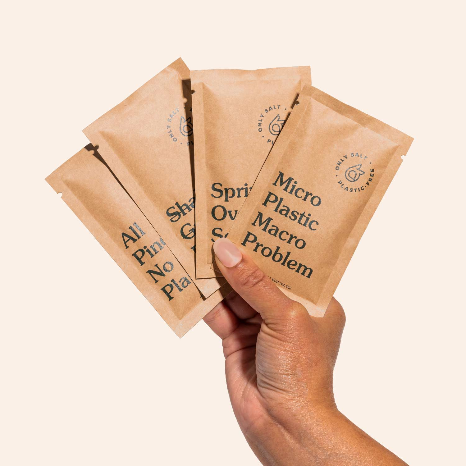 A hand fans out four packets of spring salt.