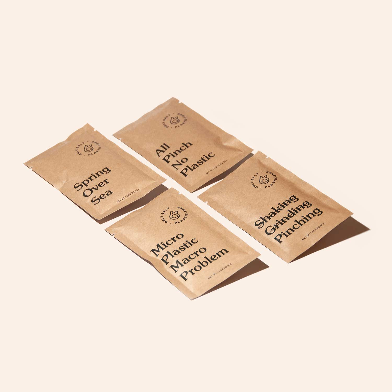 Four spring salt packets lay on a surface.