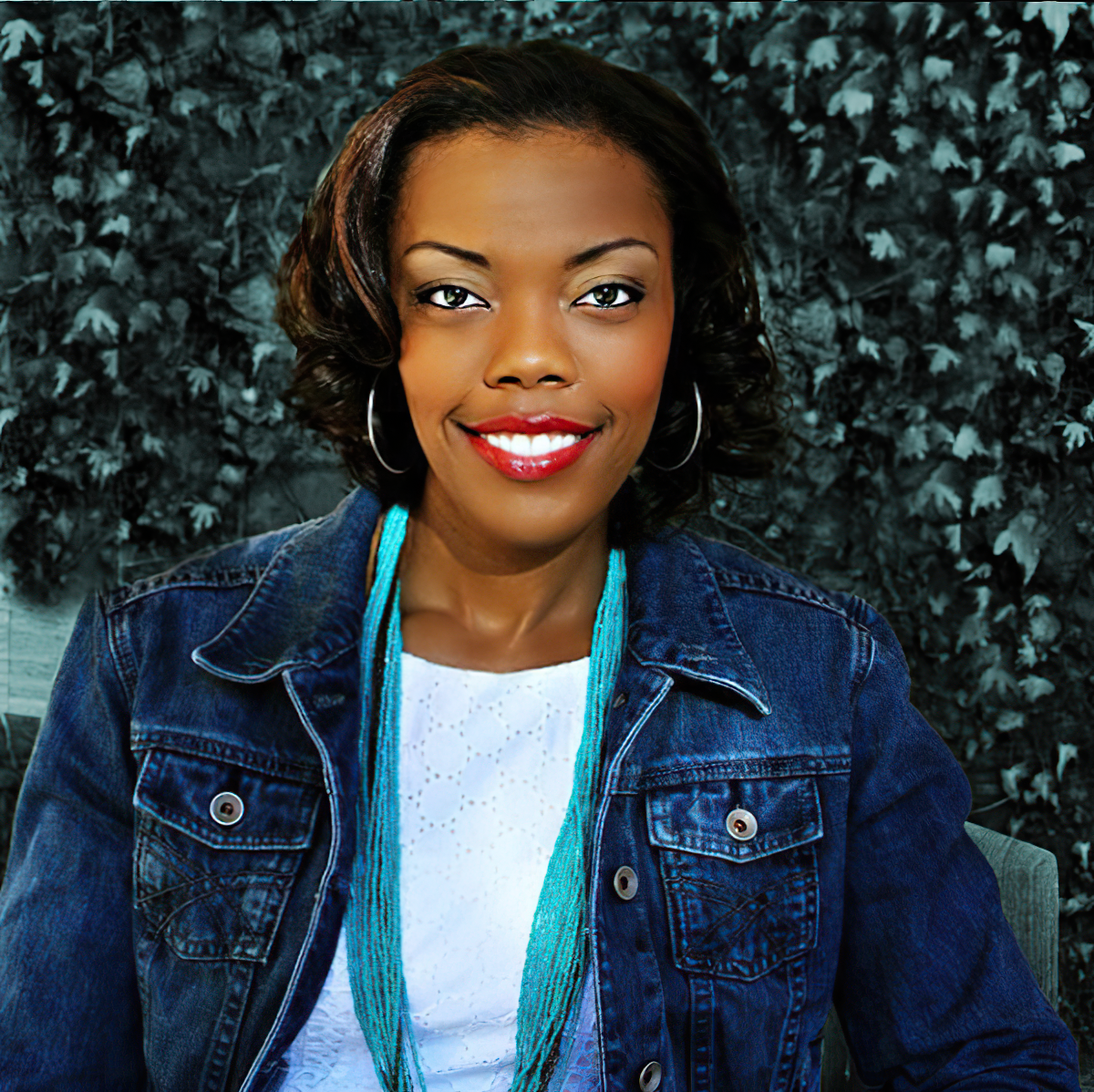 Arianne Mockabee Headshot Smiling Wearing a Jean Jacket and a Blue Scarf