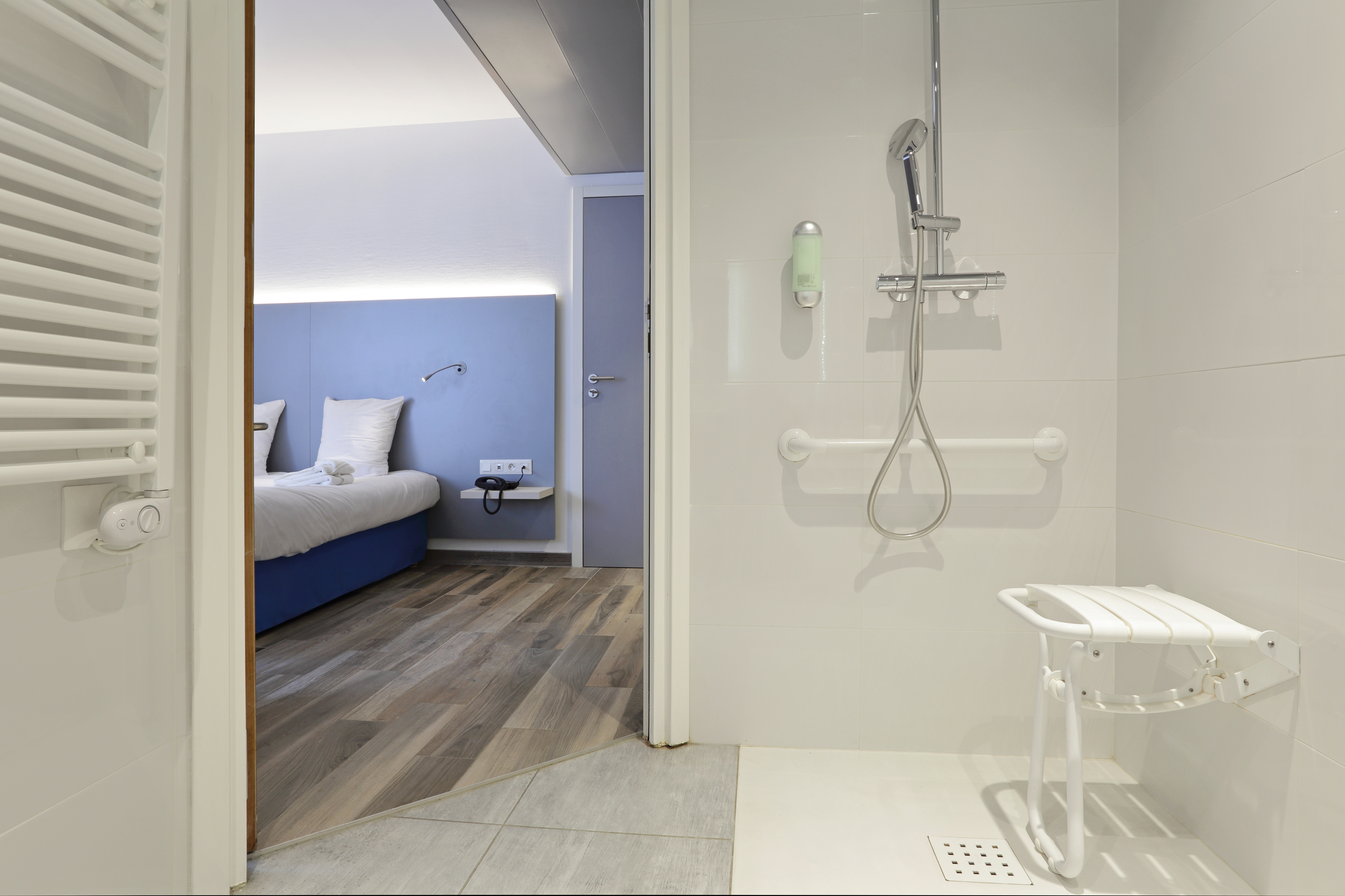 A picture of a bathroom with an accessible bathtub. The open bathroom door gives a view of a bedroom.