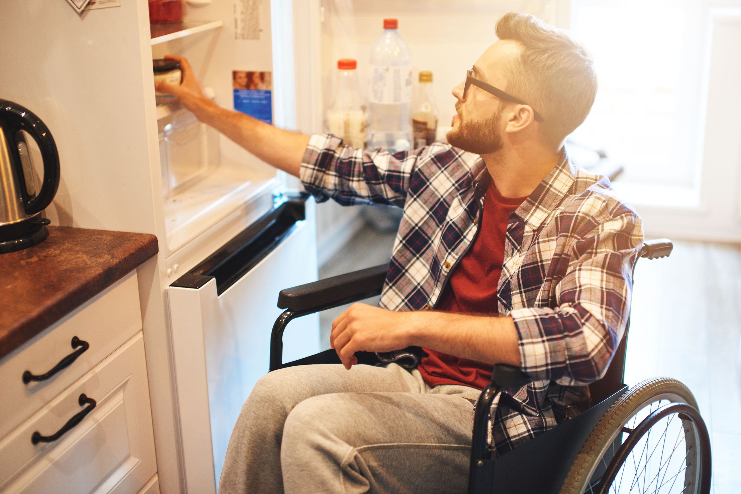 A man in a wheelchair is in his kitchen reaching for something in the cabinet.