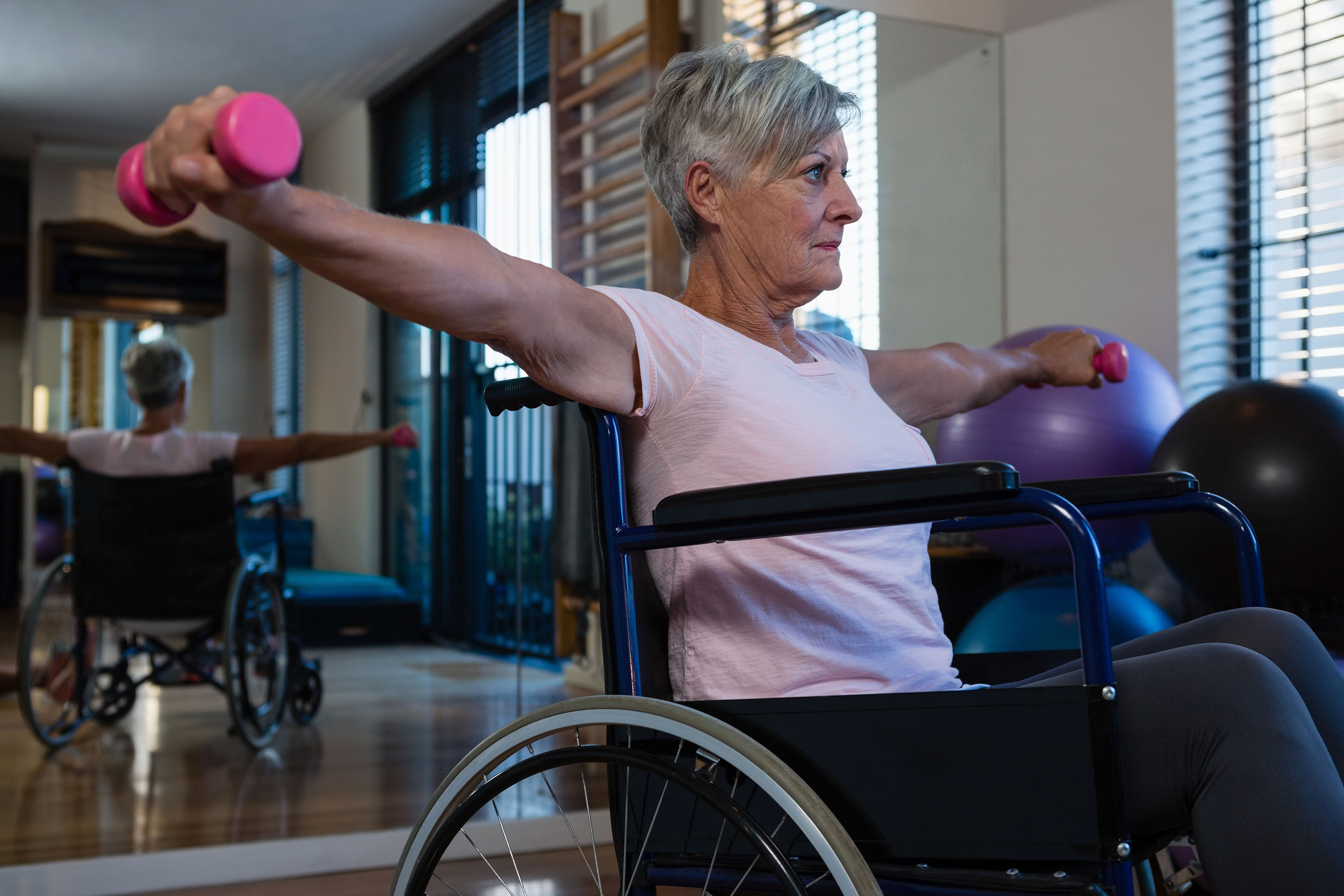 An elderly woman at the gym sits in a wheelchair and lift weights in front of a gym mirror.