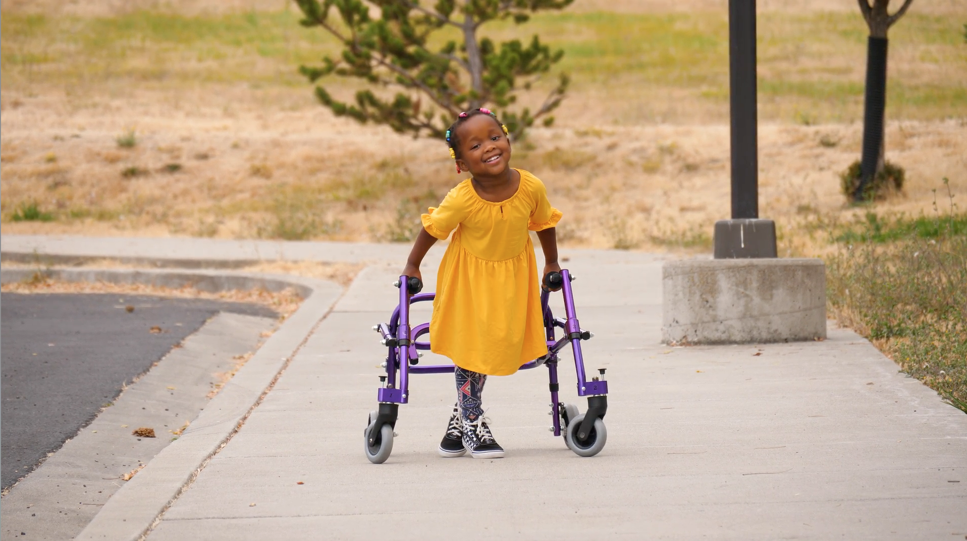 A little girl in a yellow dress in walking down the sidewalk with the assistance of a walker.