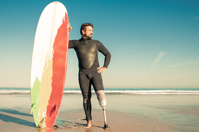 A picture of a man wearing a surfer's rash guard and a prosthetic leg stands next his surf board on the beach and looks out to the waves.