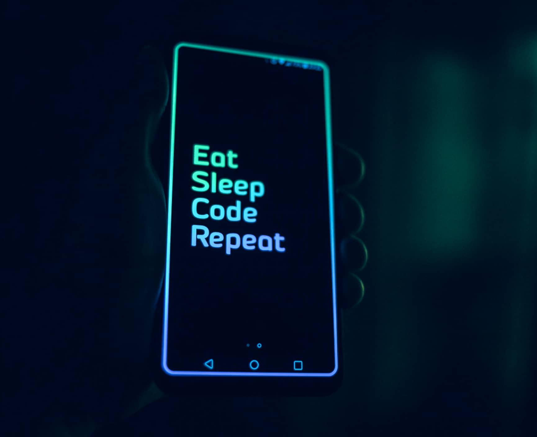 """Persona sosteniendo un celular, con las palabras """"Eat. Sleep. Code. Repeat"""""""