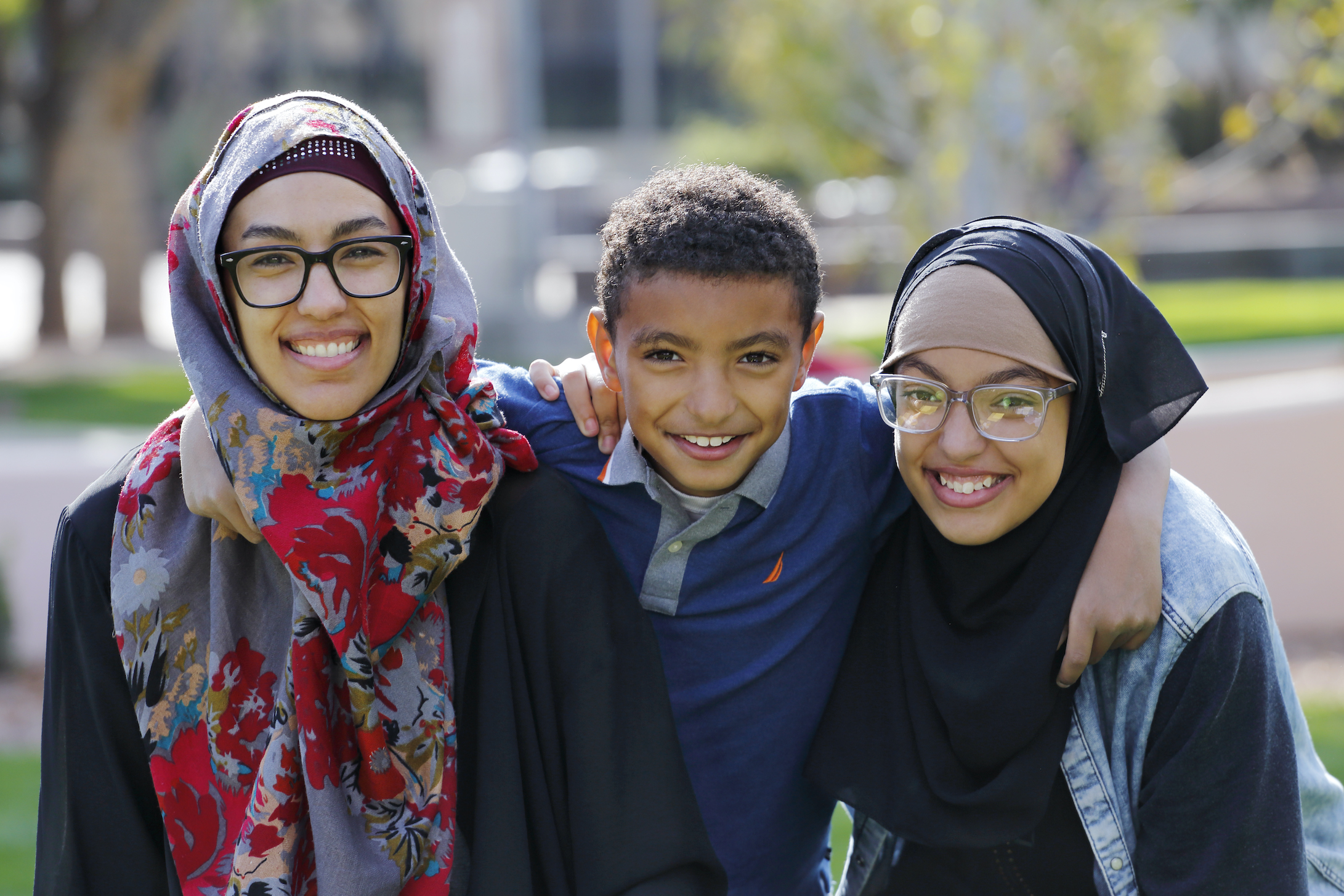 Two girls with glasses, dressed in hijab,  with a young boy, smiling