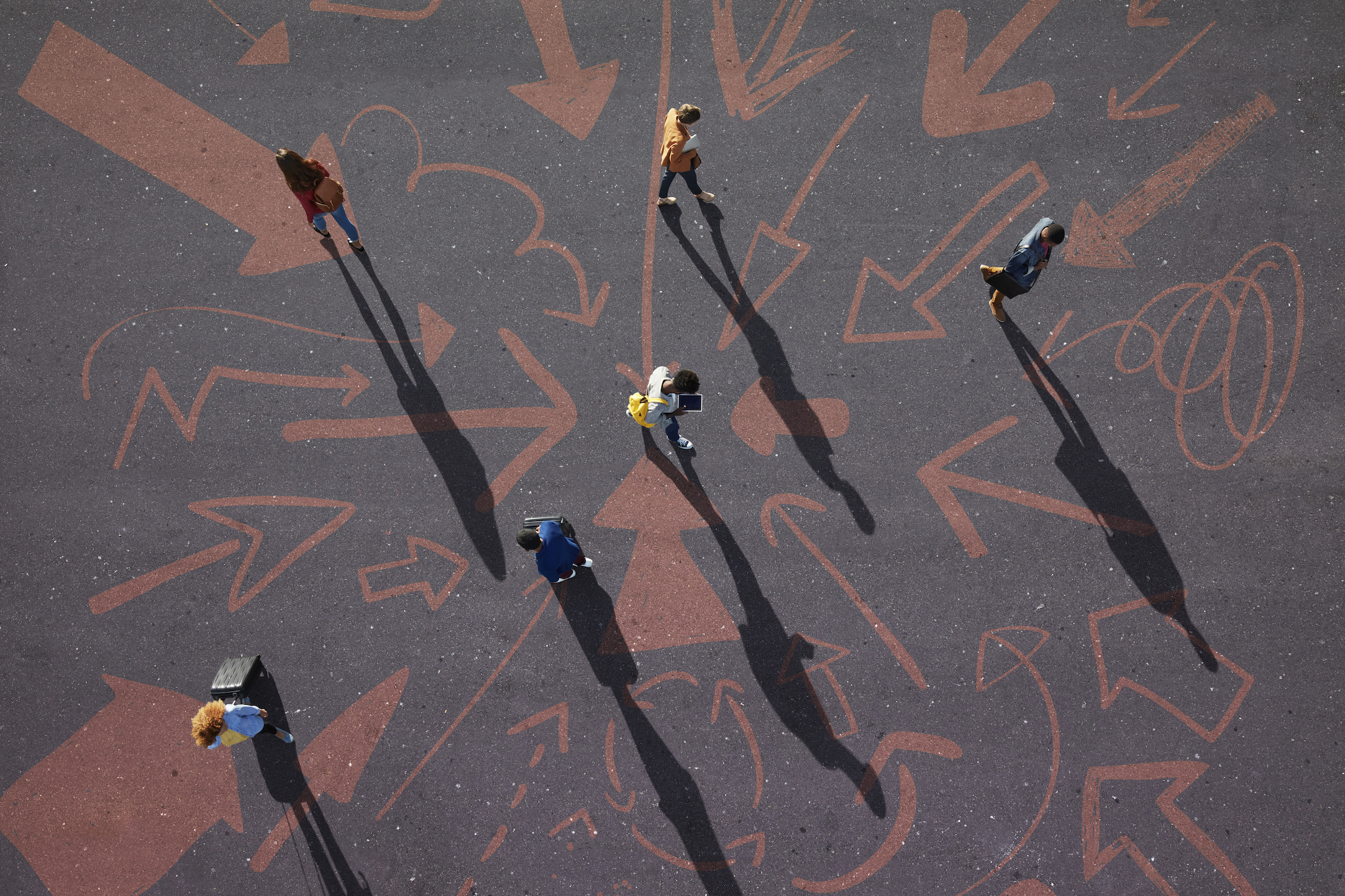 Arial view of young people walking with arrows on the ground