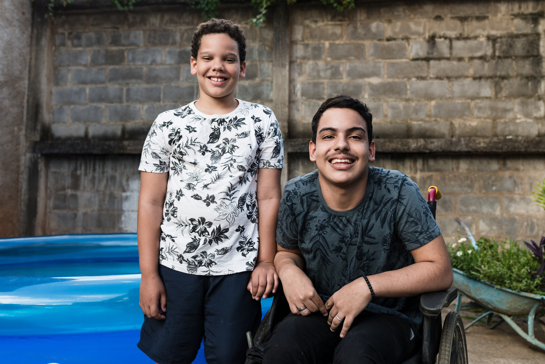 A boy in a wheelchair with a younger boy outside