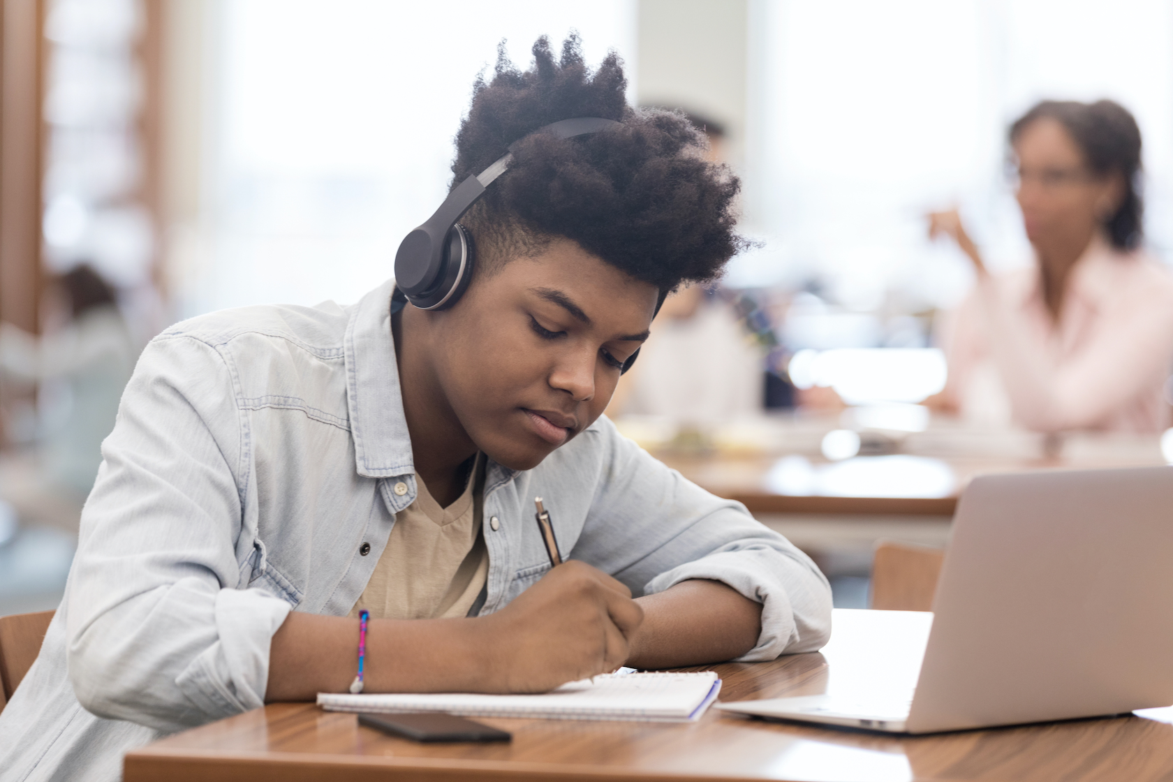 Boy working at laptop with headphones on