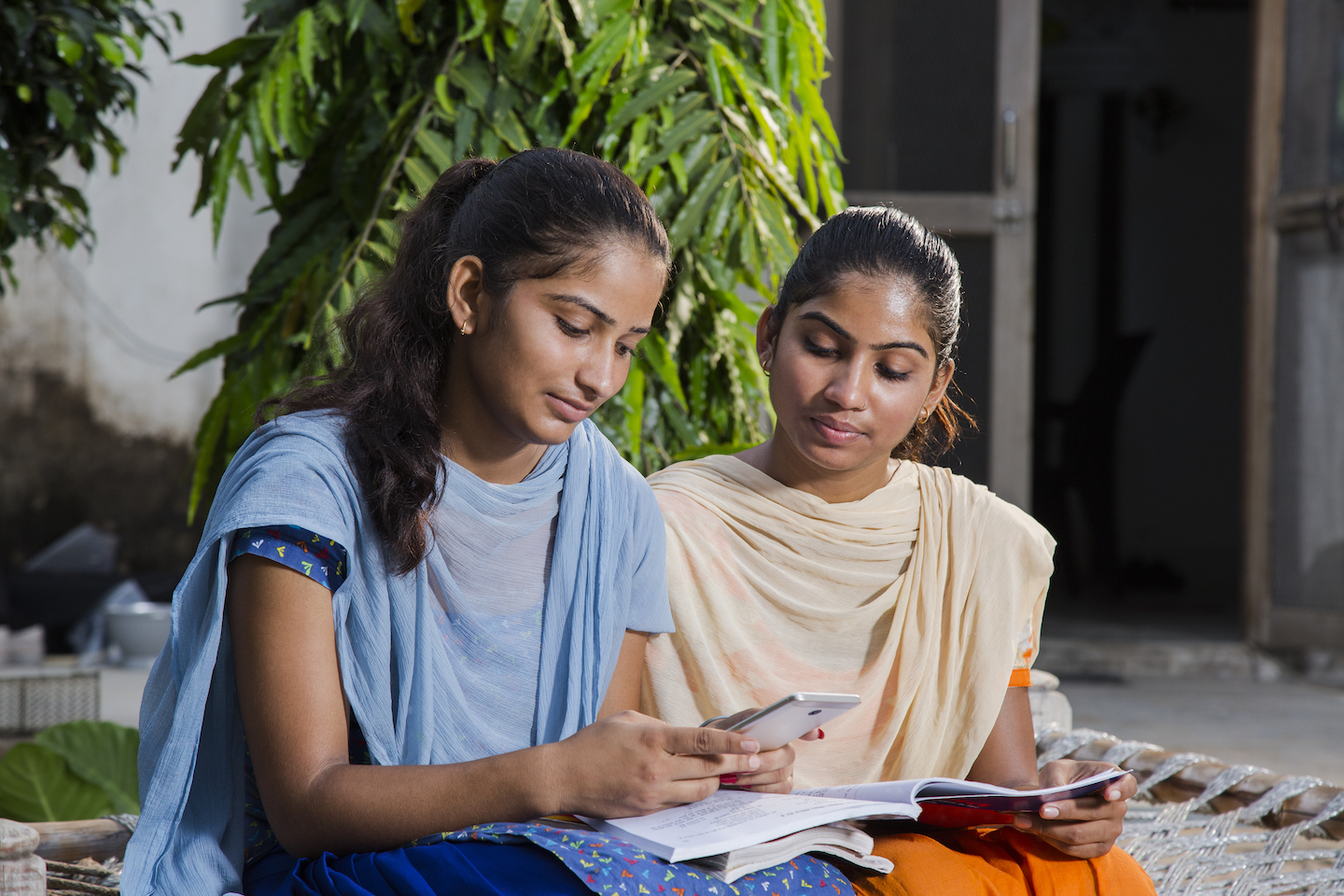 Two young women, studying and looking at a smartphone