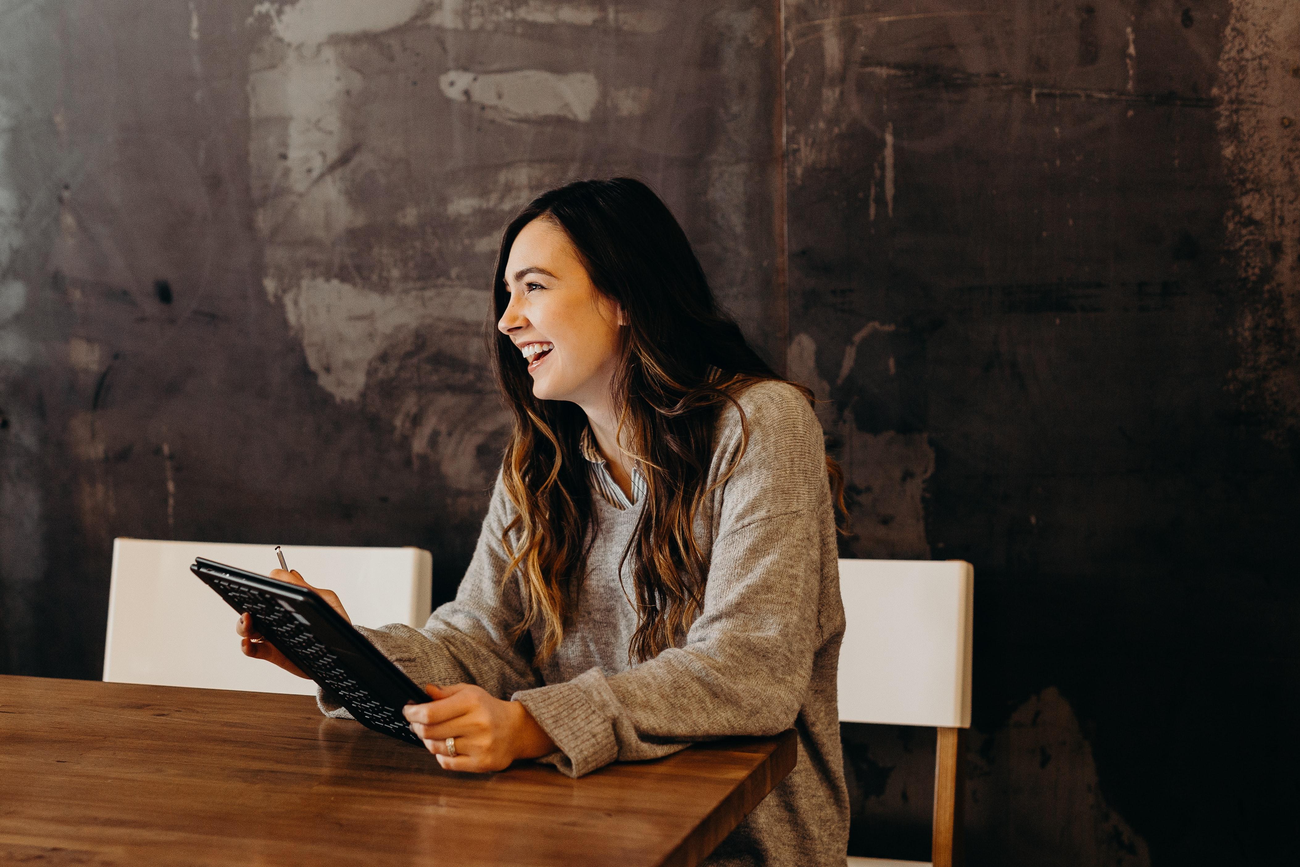 A girl smiling looking at an ipad