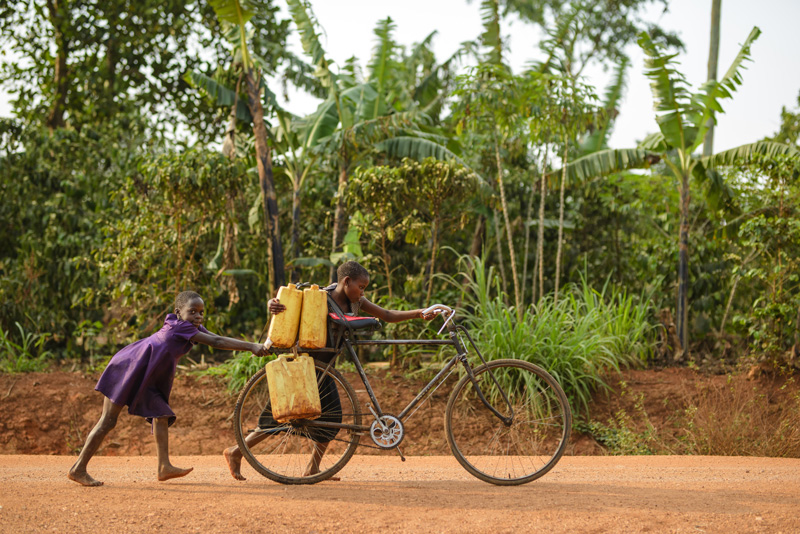 A little girl and her mom pushing a bicycle loaded with jerry cans full of water