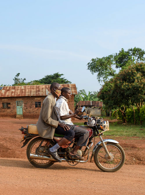 Two men riding on a motorbike past a small house