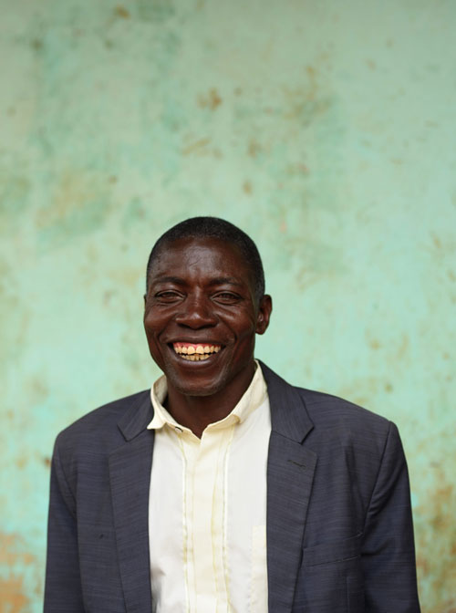 A man in a shirt and jacket standing against a green wall, smiling