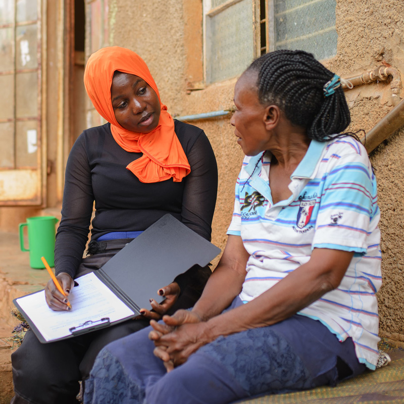 A female Water Compass staff member talking to a woman at her home about her community's needs